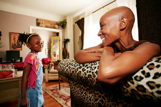 Black mother and daughter smiling in living room
