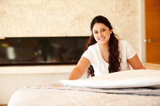 Hispanic woman making bed