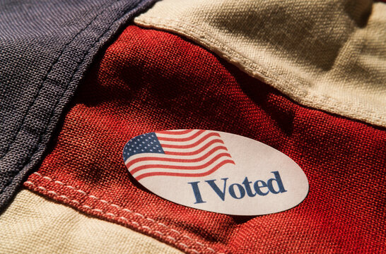 Close-up of I voted sticker on American flag