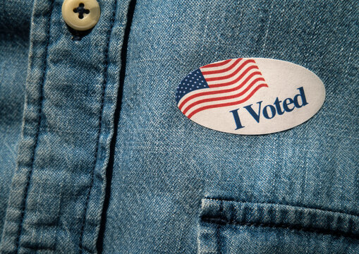 Close-up of I voted sticker on denim shirt