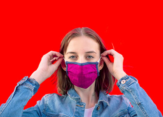 Portrait of teenage girl putting on protective mask against red background