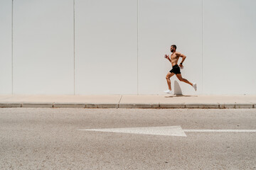 Barechested male athlete running on pavement with arrow sign on the road
