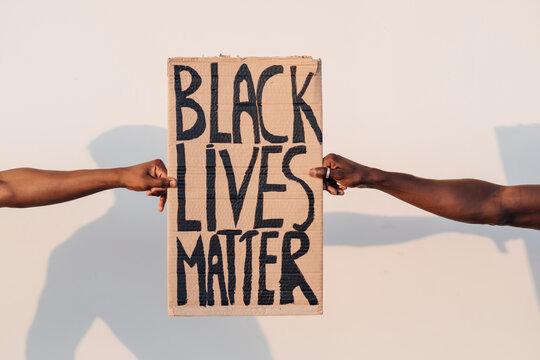 Hands holding Black Lives Matter sign