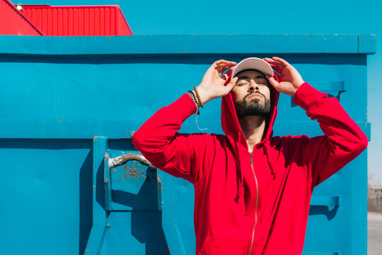 Young man wearing red hoodie, facing the sun
