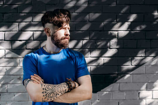 Young man with tattoo standing in front of brick wall with arms crossed