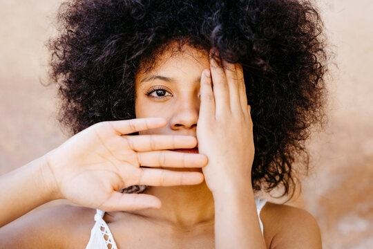 Black woman staning in front of wall, covering one eye and mouth with hands
