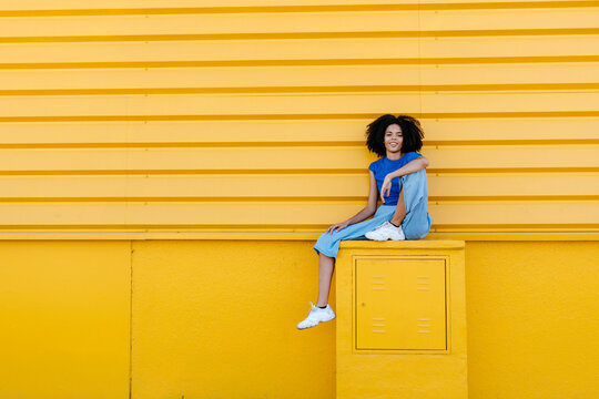 Pretty woman sitting on platform in front of yellow wall, smiling