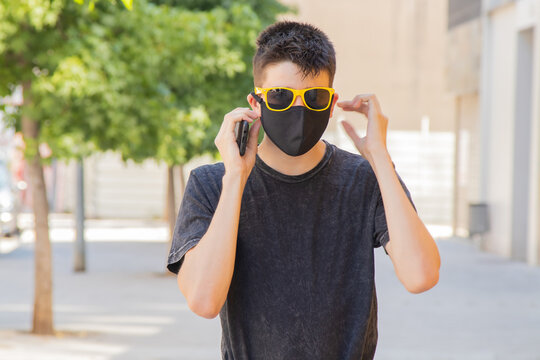 young man on the city street with face mask