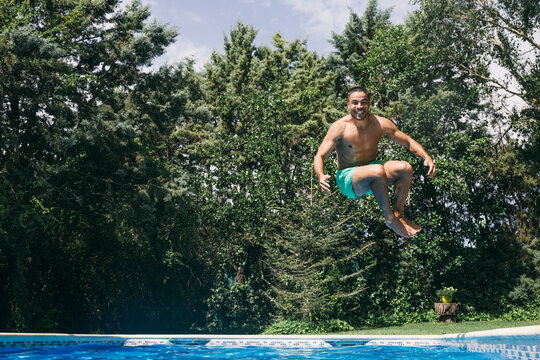 Cheerful handsome young man diving in swimming pool against trees