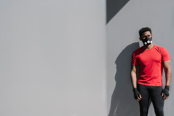 Sportsman wearing face mask standing at grey wall