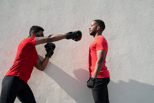 Sportsman wearing face mask and boxing against training partner standing still