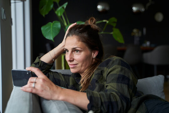 Thoughtful woman holding smart phone looking away while relaxing on sofa at home