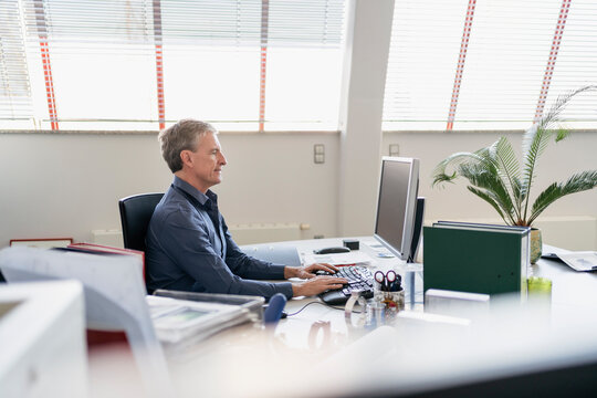 Side view of confident businessman using computer while sitting at desk in office