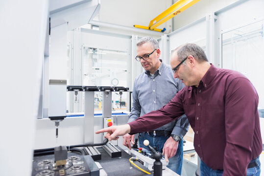 Two businessmen having a discussion at a machine in a factory