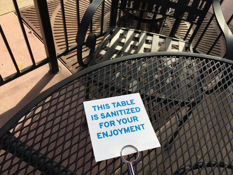 Sign on a restaurant's outdoor table informing customers that is has been sanitized.