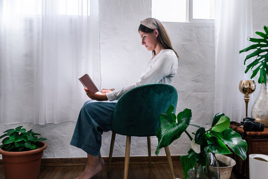 Relaxed woman reading book while sitting on chair by plants at home