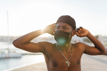 Black man with beanie putting on face mask