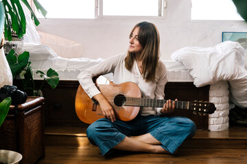 Woman sitting on the floor in front of bed with guitar