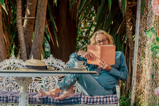 Senior woman sitting on garden bench reading a book