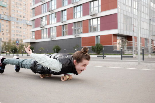 Carefree girl lying while skateboarding on road against building