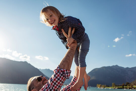 Father holding aloft cheerful daughter against blue sky at Achensee, Tyrol State, Austria