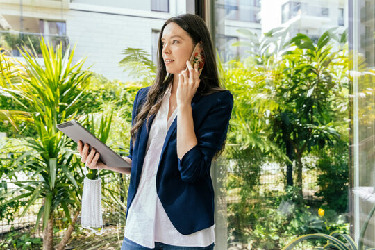 Woman with digital tablet and face mask in hand talking on the phone