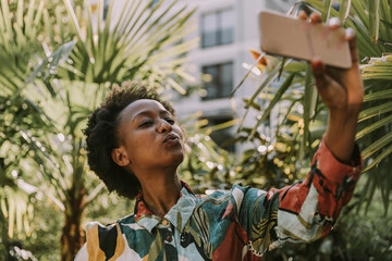 Portrait of young woman taking selfie with smartphone in garden