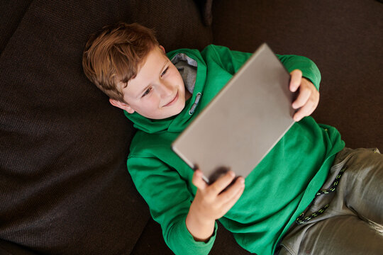 Smiling boy using digital tablet while lying on sofa at home