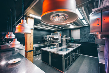 Pendant lights hanging on counter in commercial kitchen at restaurant