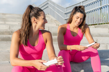 Smiling beautiful young women sitting with protein bars on steps during sunny day