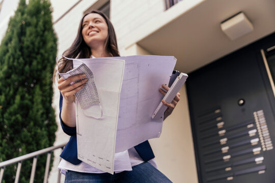 Happy woman with face mask and blue print in hand looking at outside area of house