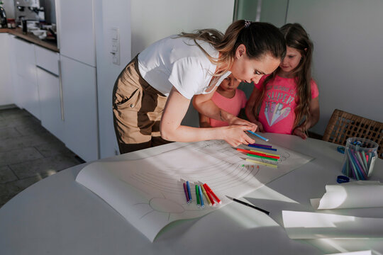 Mother assisting daughters in drawing on paper at home