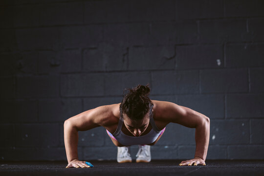Woman practicing push-up exercise at gym