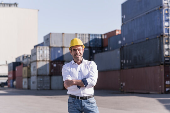 Portrait of confident businessman wearing safety helmet in front of cargo containers