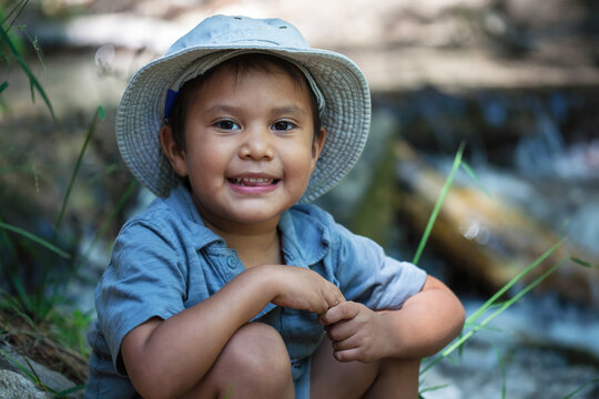 A little boy wearing his fishing hat, sitting next to the the rivers edge during summer.