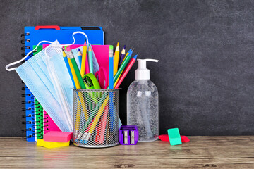 School supplies and COVID 19 prevention items on a desk against a chalkboard background. Back to...