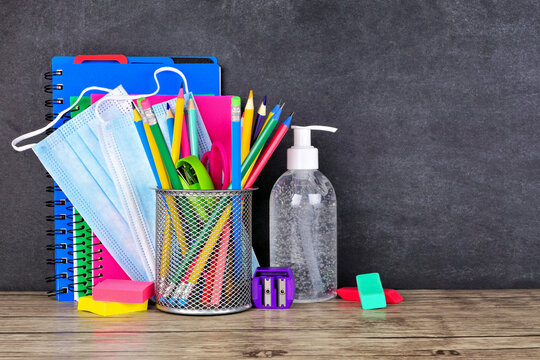 School supplies and COVID 19 prevention items on a desk against a chalkboard background. Back to school during pandemic concept.