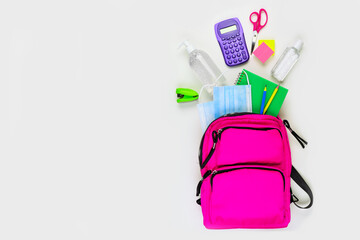 Poster Asia Country Backpack with school supplies and COVID 19 prevention items. Top view, spilling onto a white background. Back to school during pandemic concept.