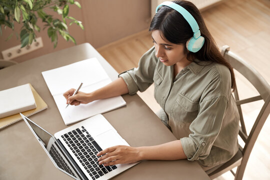 Indian girl student wear headphones learning online watching webinar class looking at laptop computer elearning remote lesson making notes or video calling virtual conference meeting teacher at home.