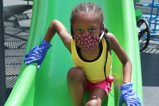 Girl on playground slide wearing face mask and gloves