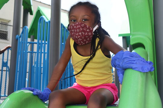 Black kid wearing fabric mask and protective gloves while playing on playground slide on summer day