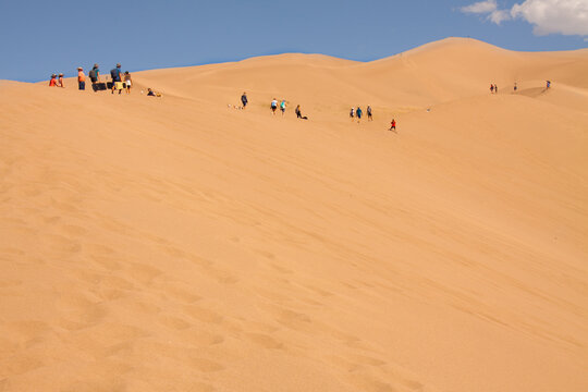 Alamosa, Colorado / USA - July 14 2020: Tourist hikers walk on giant desert sand dunes at the Great Sand Dunes National Park