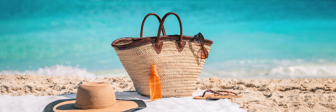 Beach essentials for summer vacation: straw bag with sunglasses, sunscreen, hat banner background. What to bring for holiday getaway.