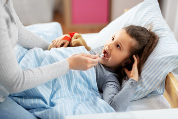 family, health and medicine concept - mother giving cough syrup to little sick daughter lying in bed at home