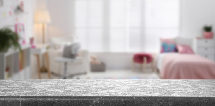 Empty grey stone table in baby room interior