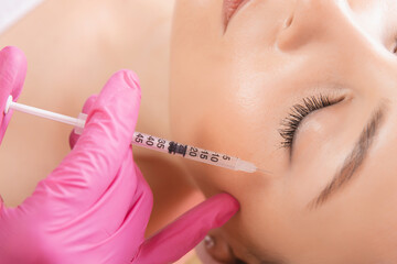 Woman getting injection procedure anti wrinkle corners of eyes forehead face skin. Beauty salon care