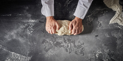 Cook or chef preparing dough for pizza bases