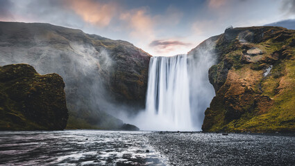 Icelandic Landscape. Classic long exposure view of famous Skogafoss waterfall with colorful sky during sunset. Skoga river, highlands of Iceland, Europe. Popular Travel destinations. Amazing nature.