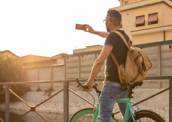 young guy seen from behind, standing on his minimalist bike, wearing his backpack, makes a selfie with his smartphone at sunset