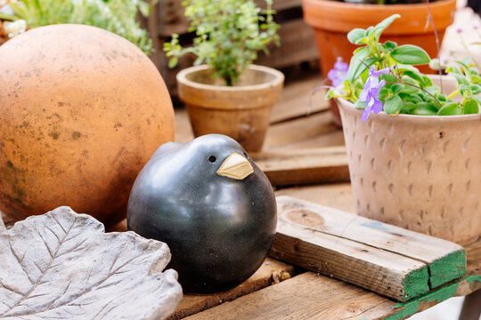 Garden Table decoration with ceramic blackbird and flowerpot showing gardener lifestyle and home backyard detail